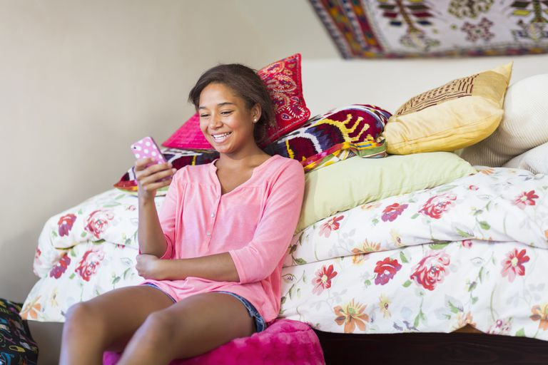 teenage girl using cell phone in bedroom