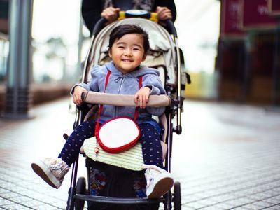 Toddler girl smiling joyfully in the stroller