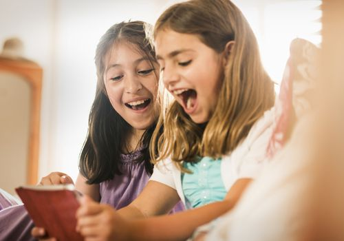 Tween girls laughing while looking at a tablet