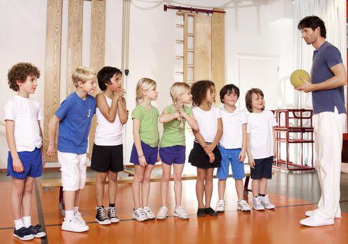 Young schoolchildren and gym teacher at school