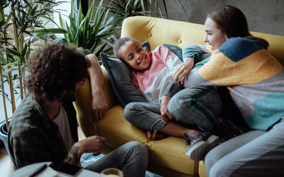 Foster parents watching TV with foster daughter