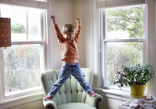 hyperactive child standing on arms of chair in living room