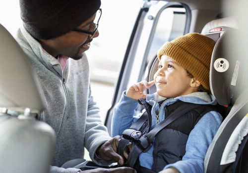 man putting child into his carseat