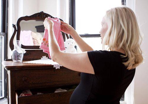 Pregnant woman folding baby dress next to dresser