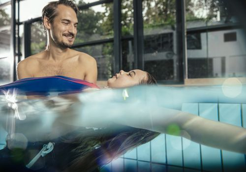 Man helping young girl learn how to swim in indoor swimming pool