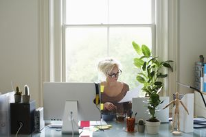 Young woman reading paperwork at desk in home office