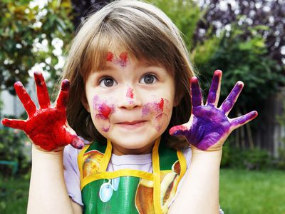 little girl with paint on hands and face