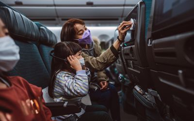 mom disinfecting tv screen for child on an airplane
