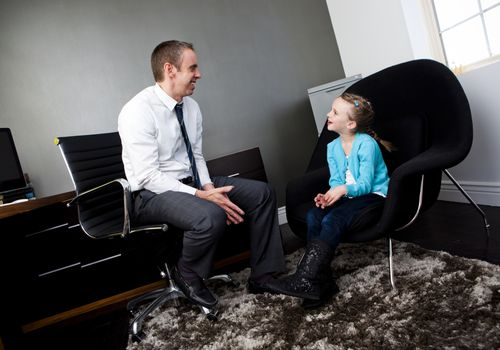 Child psychologist talking to a little girl in an office