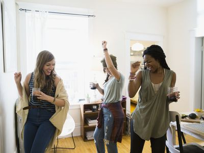 Friends drinking wine and dancing in living room supporting fertile and infertility friends