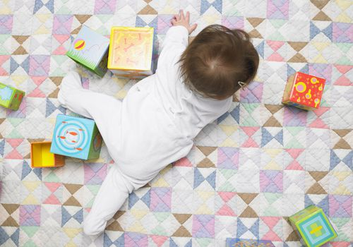Overhead view of a baby in a white outfit playing with blocks on a colorful quilt.