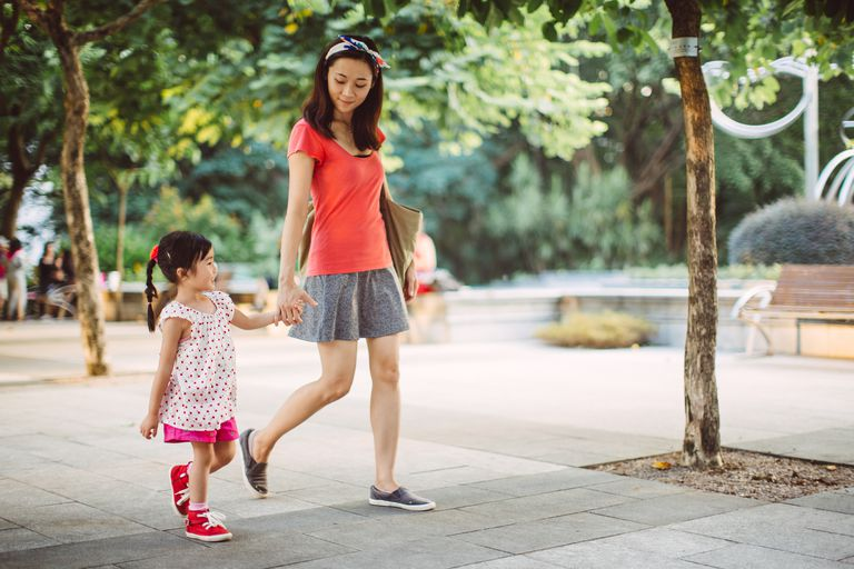 Mom and toddler strolling joyfully in park