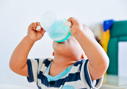 The little boy drink from a cup.