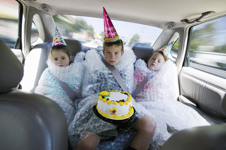 2 kids in the backseat of a car wrapped in bubble wrap
