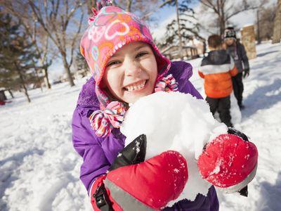 Snow play ideas - girl holding snowball outdoors