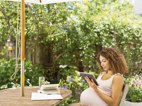 Pregnant woman reading in garden
