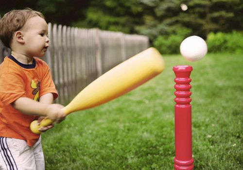 toddler boy playing tee-ball