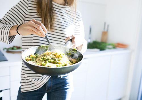 Young woman holding pan with vegan pasta dish