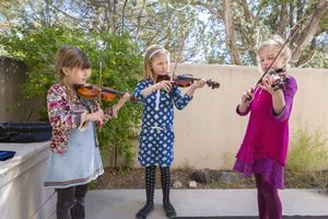 Three girls playing violin outside