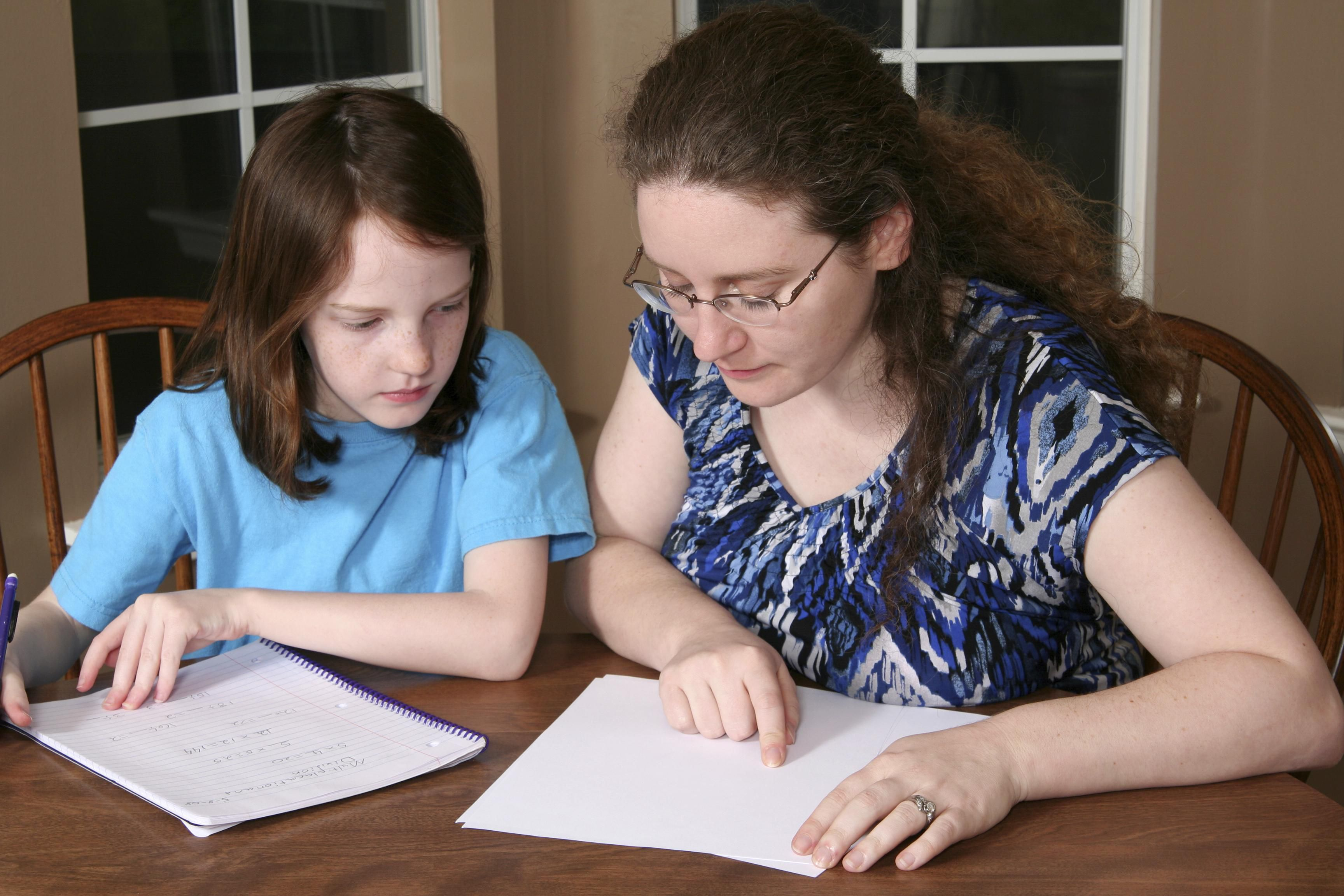 Woman tutoring a child with schoolwork