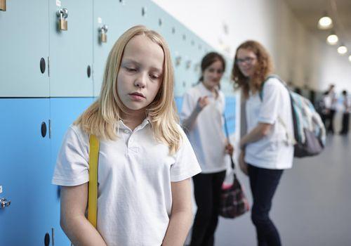 Upset girl standing in a school hallway; two girls teasing