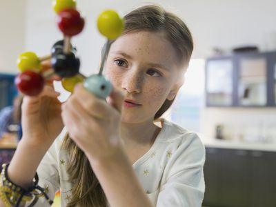 A student examining a molecule model.