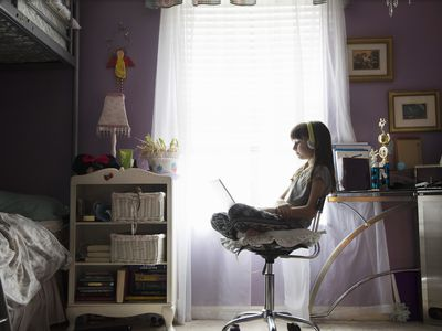 Young girl in bedroom using laptop with headphones