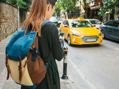 college student checking phone waiting on cab