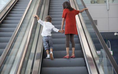 Boy and girl standing on escalator.
