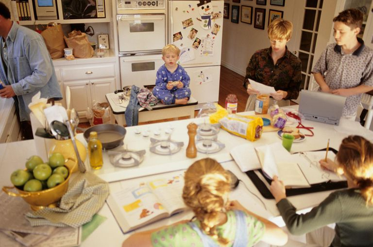 Large family in kitchen in morning, daughters (8-9) doing school work