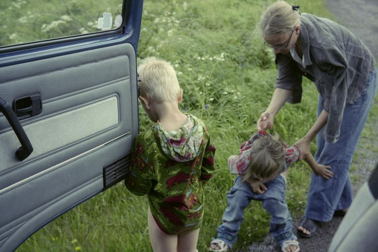 A mother helping her children to pee on a roadside, Sweden