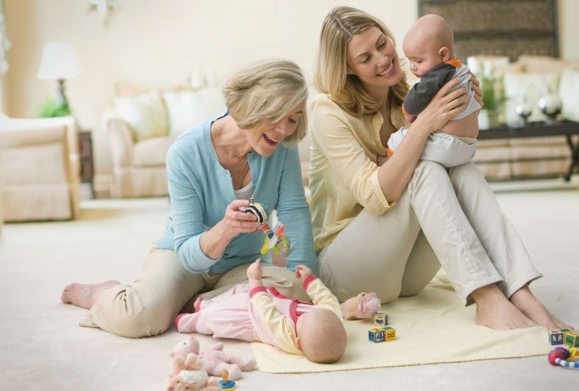 Caucasian grandmother and mother playing with baby twins