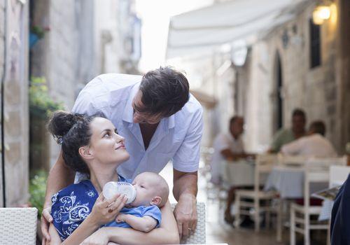 Woman feeding a baby at a sidewalk cafe