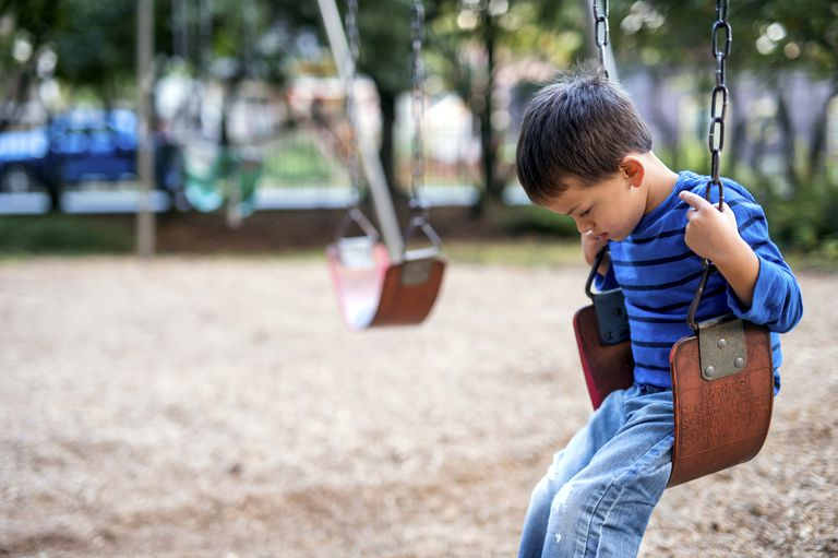 Young boy sitting on swings alone looking sad