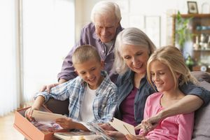 Caucasian couple looking at photographs with grandchildren