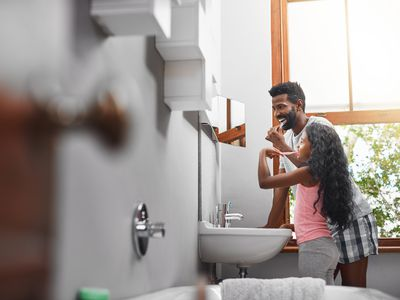 dad and daughter brushing teeth together