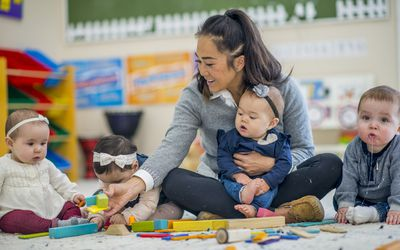Pre school teacher playing with babies