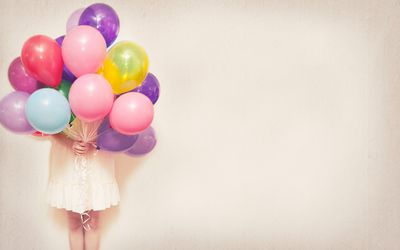 Girl holding a bundle of balloons in front of her face