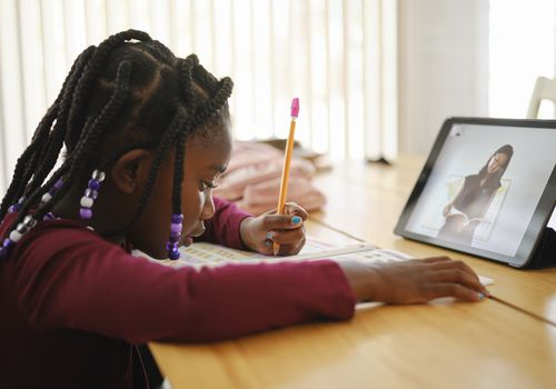 A girl sits at a table doing online school writing with a pencil.