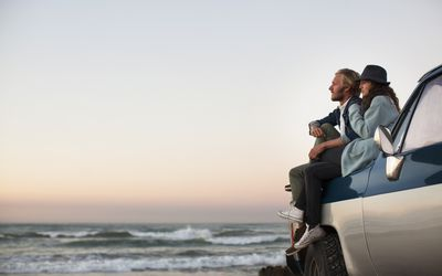 couple sitting on their car looking out over the ocean