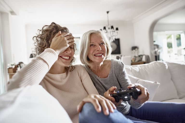 Happy mother and adult daughter playing video game at home
