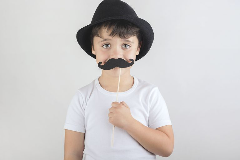 Boy wearing hat and holding a fake mustache to his face