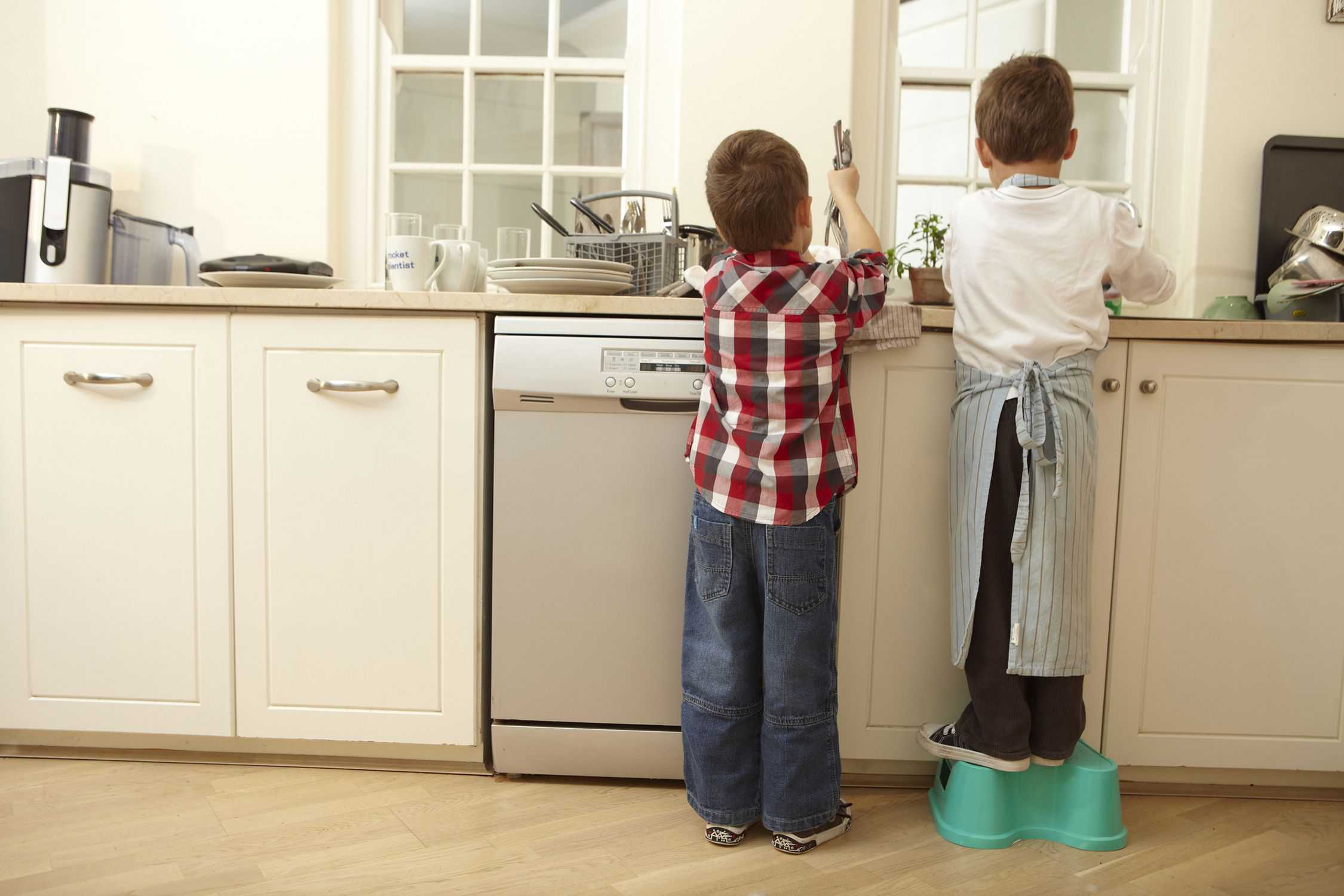 young boys washing dishes at sink
