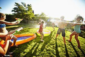 Kids having fun with squirt guns in a backyard