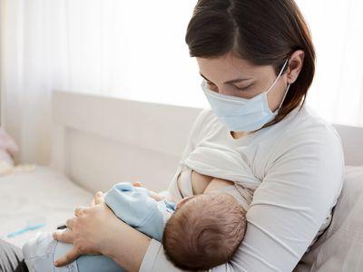 Mom wearing a mask nursing a baby