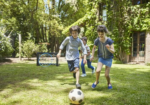 Group of 7 Year Old Footballers Playing in Family Backyard