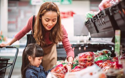 Mom & daughter doing grocery shopping for fresh fruit in supermarket