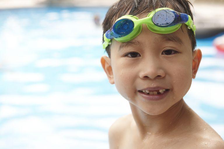 Swim lessons - Little boy with swim goggles near pool