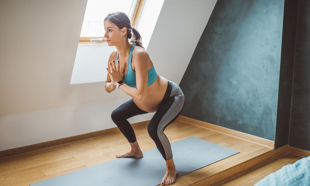 pregnant woman exercising at home in a squat