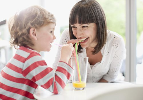 mom drinking orange juice with toddler boy